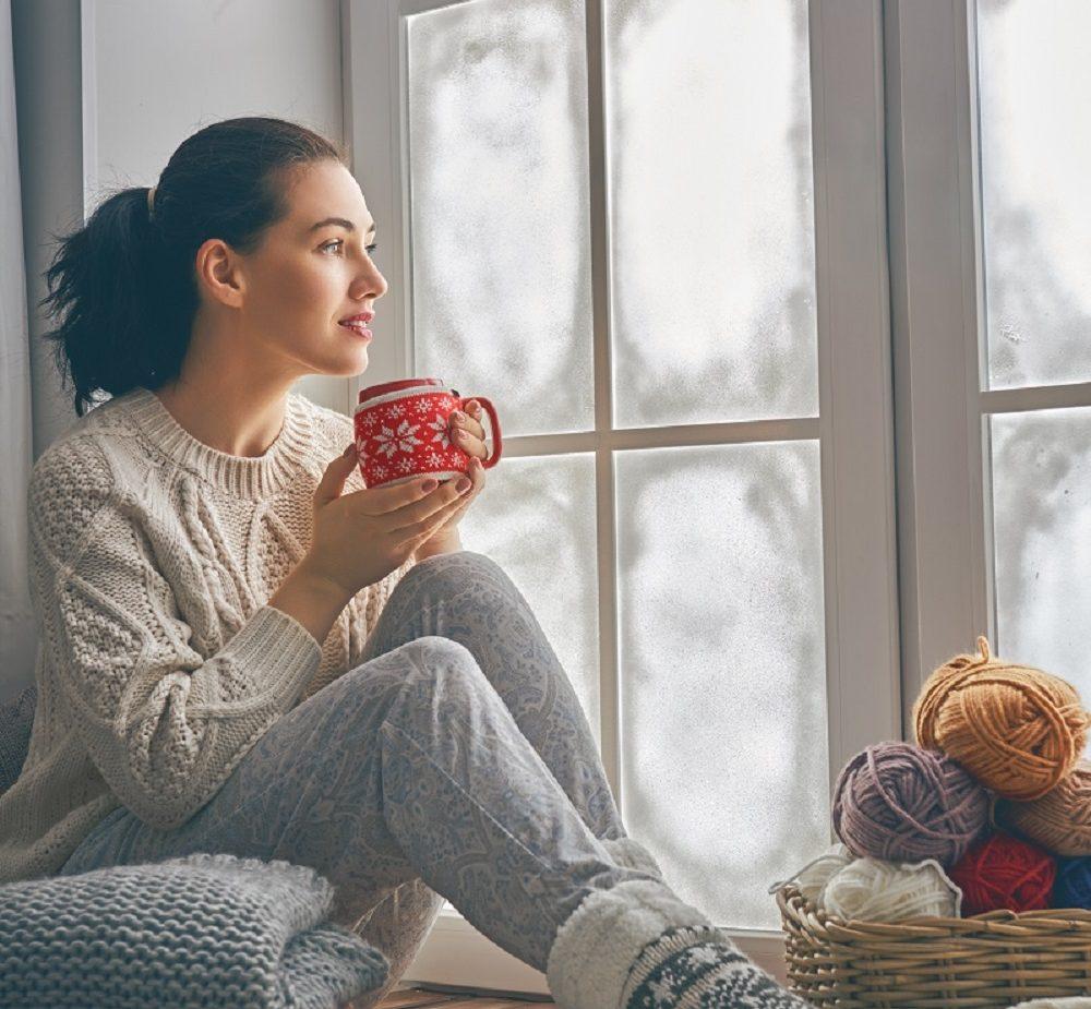 Vrouw bij het raam in de winter - isolerende raamfolie